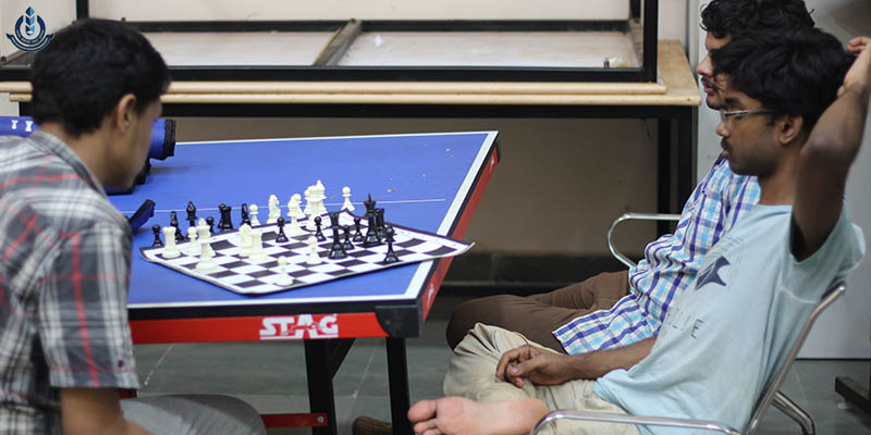 Two players playing a chess game, chess board and pieces placed on a blue coloured table and one person viewing it.