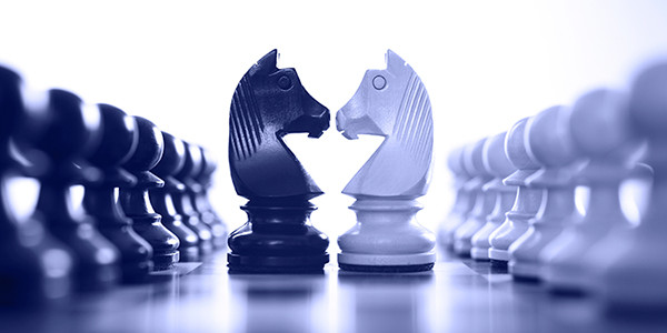 A chessboard in the background with black and white pawns higlighted in the front.